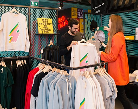 Man looks at a sweatshirt while female shopkeeper looks on at The Student Hotel shop Amsterdam West