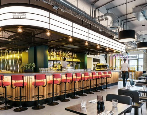 Central bar with pink stools surrounded by dining tables at The Commons restaurant Amsterdam West