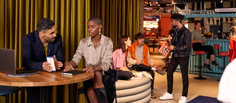 Group sits on bar table near the BedTalks event space at The Student Hotel Amsterdam City