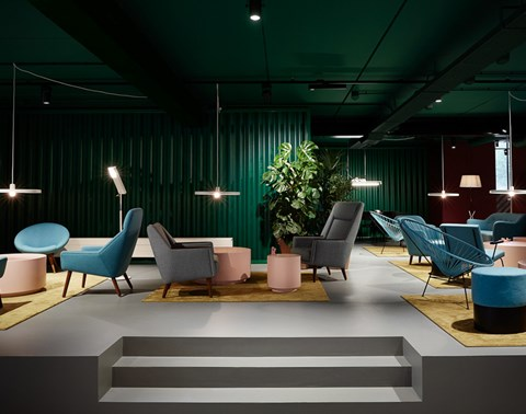 Designer lounge at The Student Hotel Amsterdam City with plush chairs and small tables