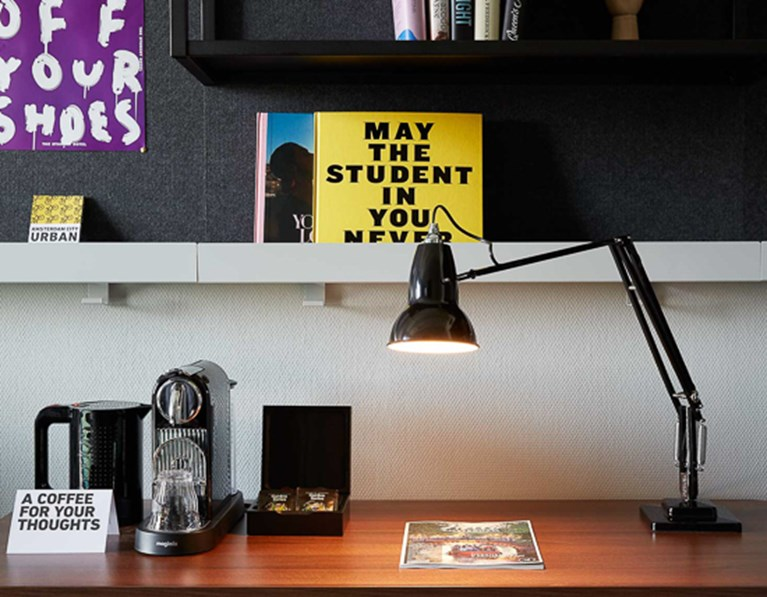 Desk in a guest room at The Student Hotel Amsterdam City with coffee machine, lamp and shelving