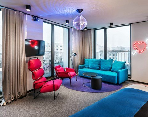 Red accent chairs, blue sofa, disco ball and balcony of the Play Room at The Student Hotel Berlin