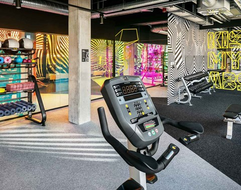 Designer interior of The Student Hotel Berlin gym with exercise machine, weights and foam rollers