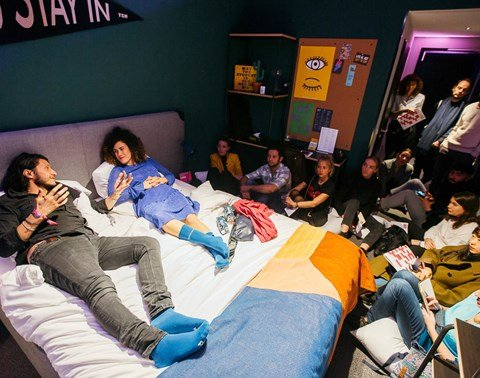 Speakers sit on bed surrounded by an audience in a guest room for BedTalks Festival Berlin