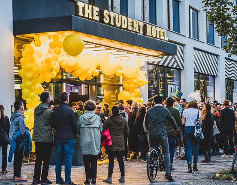 Crowd gathers around the entrance to The Student Hotel Berlin, which is decorated in yellow balloons