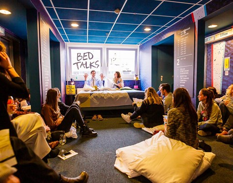 Speakers sit on bed surrounded by an audience at a BedTalks event at The Student Hotel Dresden