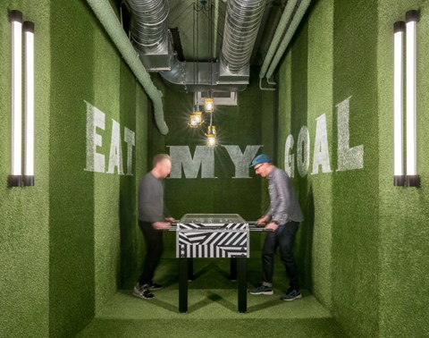 Two men play fussball in a small games room with grass-like walls at The Student Hotel Dresden