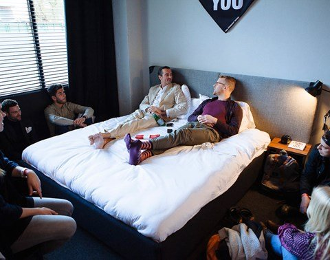 Audience crowd around a bed in a guest room at an event at The Student Hotel Amsterdam City