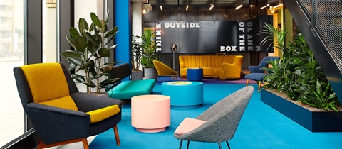 Colourful chairs, tables and carpet in the lounge of The Student Hotel Eindhoven lobby
