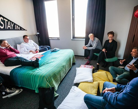 Speakers sit on bed surrounded by an audience in a room at an event at The Student Hotel Eindhoven