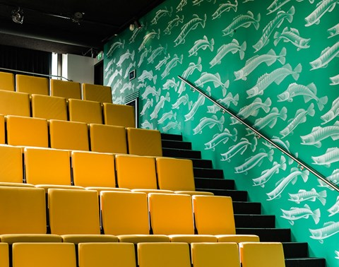 Yellow auditorium seating at The Student Hotel Eindhoven with wall mural of fish