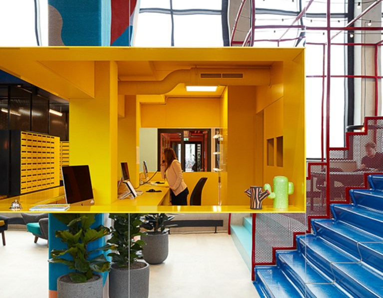 Yellow reception area and blue staircase in the lobby of The Student Hotel Eindhoven