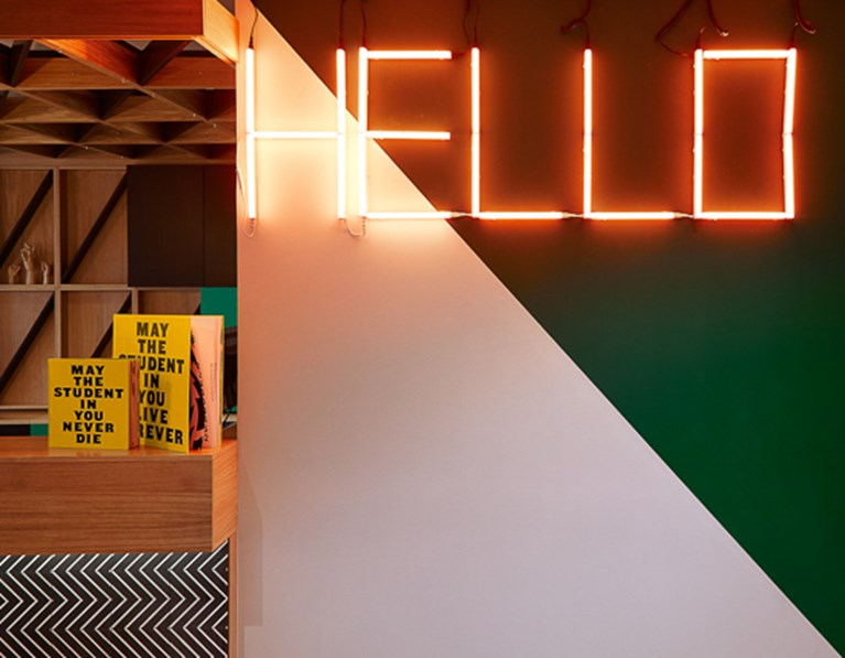 "Neon sign spelling ""Hello"" hangs on a wall at The Student Hotel Paris La Défense"