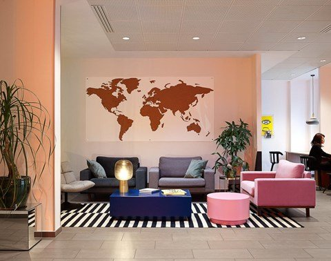 Pink and blue lounges and world map art in the lobby of The Student Hotel Paris La Défense
