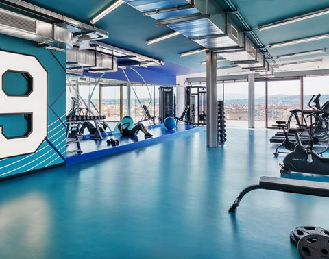 Guest does sit ups in rooftop gym with city views at The Student Hotel Florence Lavagnini