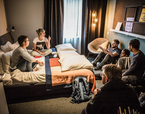 Group gather on the bed and floor of a guestroom to talk at The Student Hotel Groningen