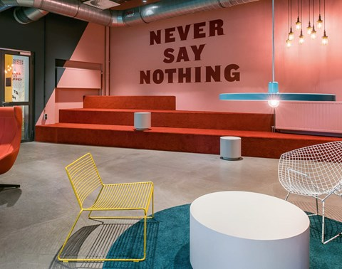 "Pink and orange lounge area with ""Never say nothing"" sign at The Student Hotel Rotterdam"