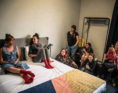Speakers sit on bed surrounded by an audience in a hotel room at The Student Hotel Rotterdam