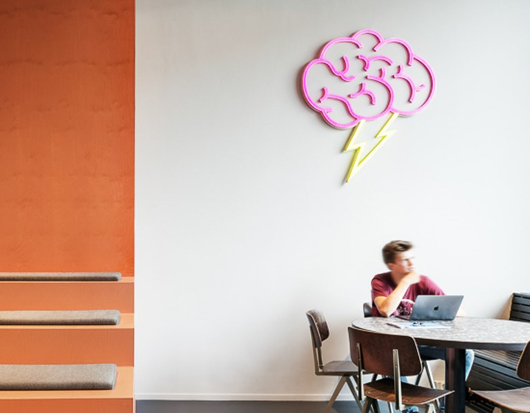 Man sits at desk thinking with brain fluoro light hanging above at The Student Hotel Rotterdam