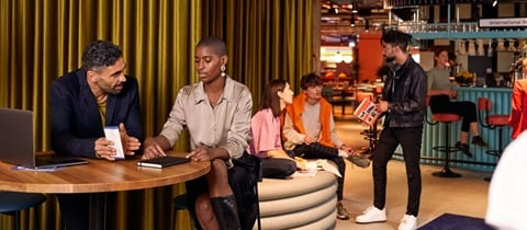 Group sits on bar table near the BedTalks event space at The Student Hotel Maastricht