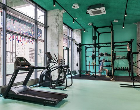 Green gym with weights and cardio equipment at The Student Hotel Maastricht