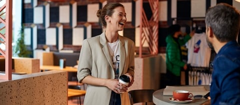 Woman in beige blazer holds coffee and laughs at The Student Hotel Bologna
