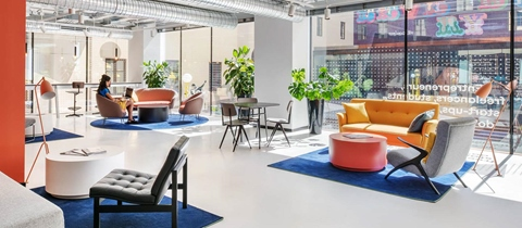 Women works from a pink chair in the open-plan workspace with sofas at The Student Hotel Florence