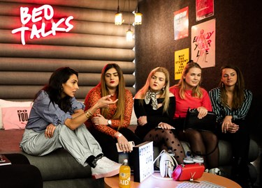 Five girls talk on a bed beneath a 'BedTalks' neon sign on The Student Hotel Delft