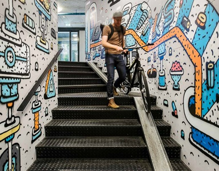 Guest wheels his bike down a mural-lined staircase with animation-style art