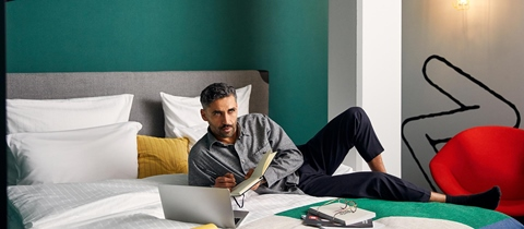 Bearded man writes in notebook while lying on his hotel room bed with laptop open