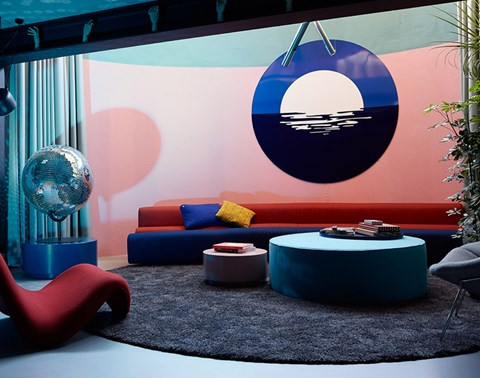 Guestroom at The Student Hotel with circular couch, giant disco ball and retro red recliner