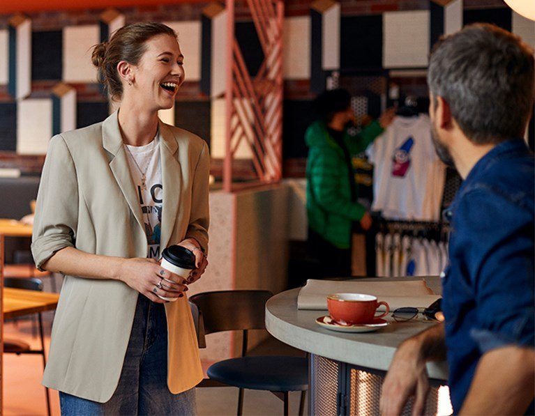 Woman in beige blazer laughs with a male friend while holding a takeaway coffee cup